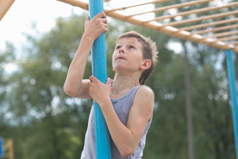 Подросток в футболке взбирается на гимнастическом поляке стоковое фото