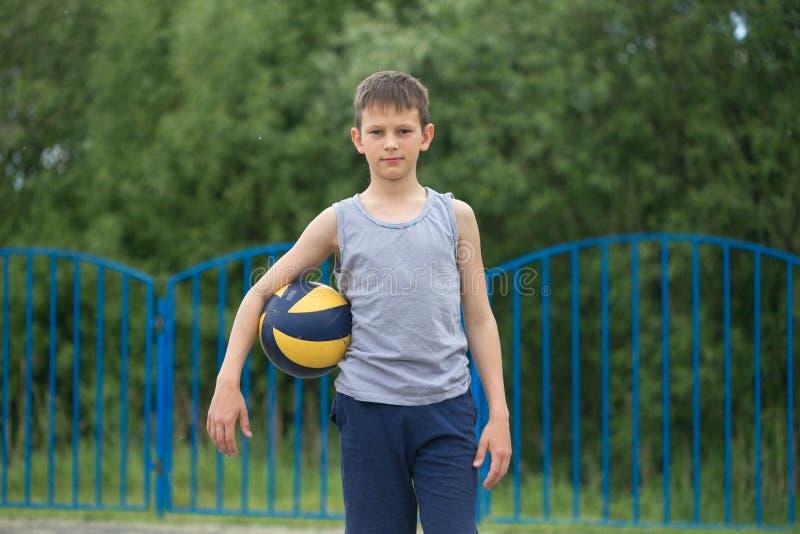 Подросток в футболке и шортах играя с шариком стоковое изображение rf