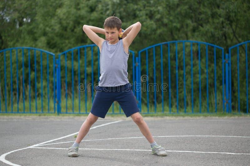 Подросток в футболке и шортах играя с шариком стоковое фото rf