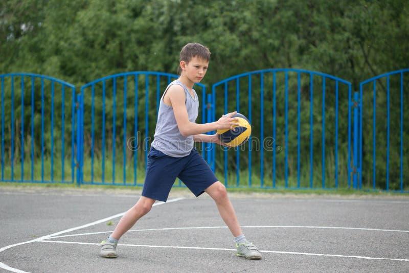 Подросток в футболке и шортах играя с шариком стоковые фото