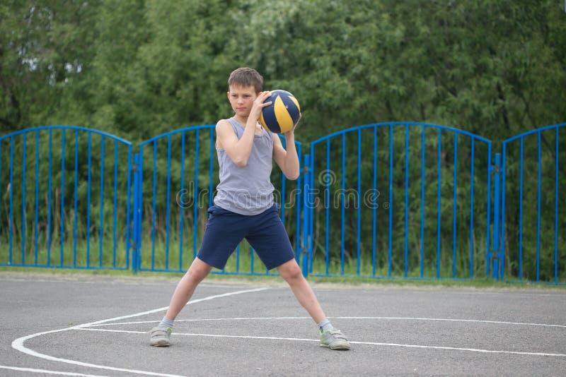 Подросток в футболке и шортах играя с шариком стоковые фотографии rf