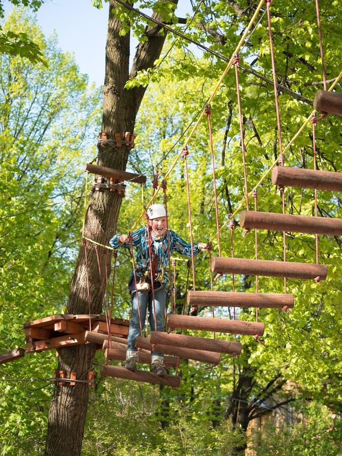Подросток в шлеме и с мальчиком веревочки безопасности идет на висячий мост сделанный вносит дальше запачканную предпосылку в жур стоковые фото