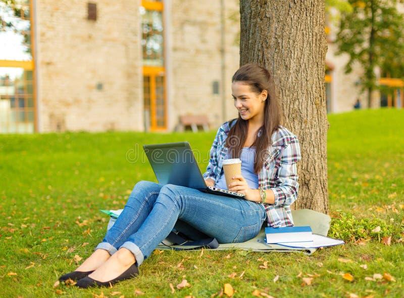 Подросток в eyeglasses с компьтер-книжкой и кофе стоковое фото