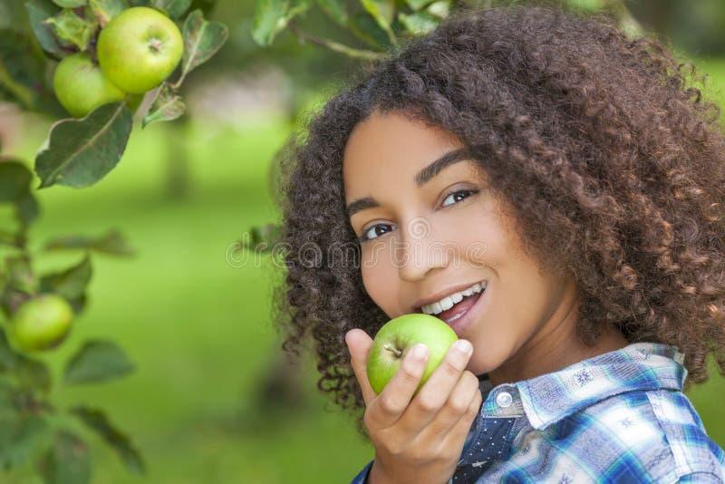 Подросток девушки смешанной гонки Афро-американский есть Яблоко стоковые изображения