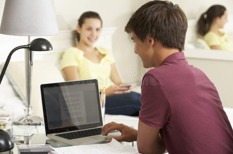 Подросток изучая на столе в спальне с девушкой в предпосылке стоковые фото