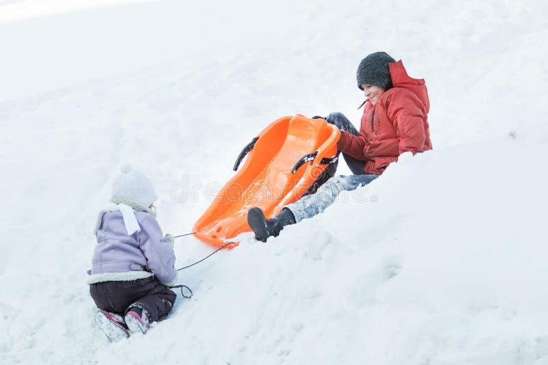 Подросток имея потеху зимы пока играющ с его сестрой отпрыска outdoors на холме снега стоковая фотография