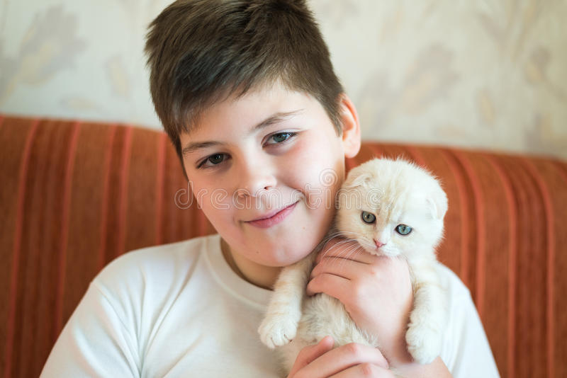 Подросток мальчика держа котенка в ее оружиях стоковое изображение rf