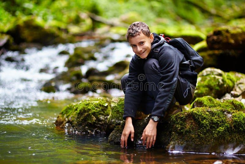Подросток моя его руки в реке стоковая фотография