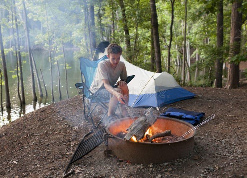 Подросток располагаясь лагерем с огнем лагеря стоковые изображения rf