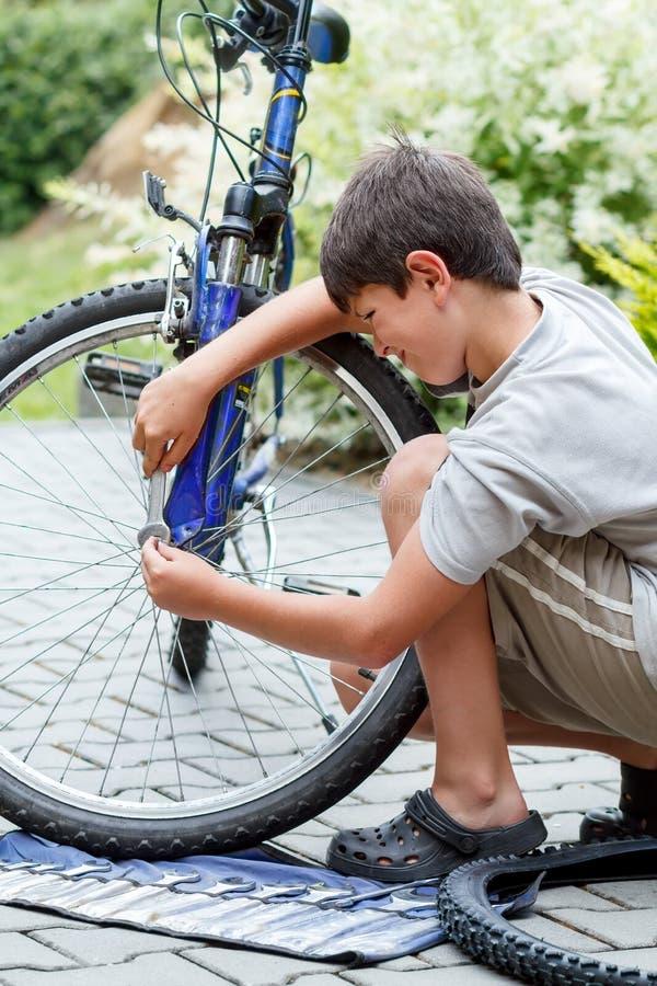 Download Подросток ремонтируя его велосипед, изменяя сломанная покрышка Стоковое Изображение - изображение насчитывающей покупщик, спорт: 33736783