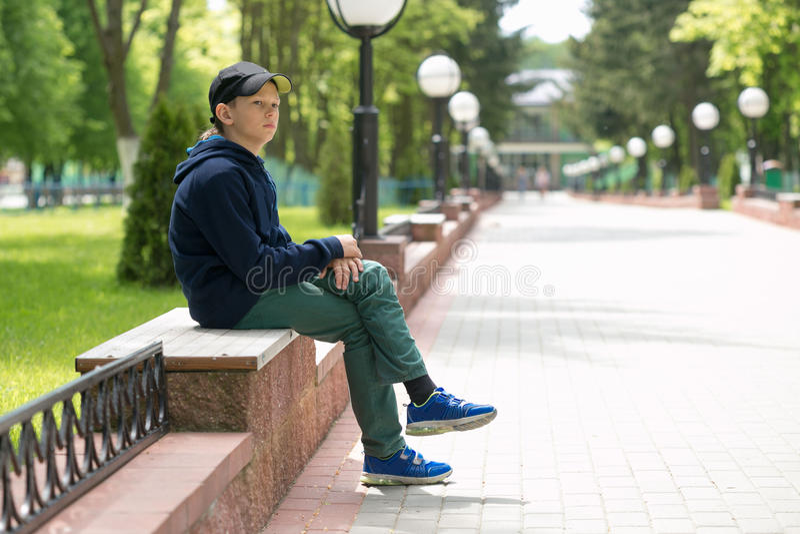 Подросток сидит на стенде в парке лета стоковое фото