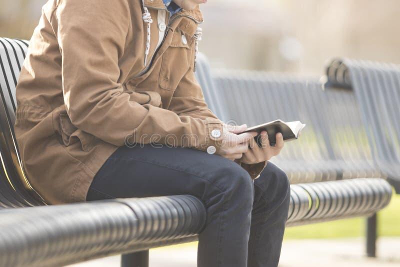 Подросток сидя на библии чтения стенда стоковое фото