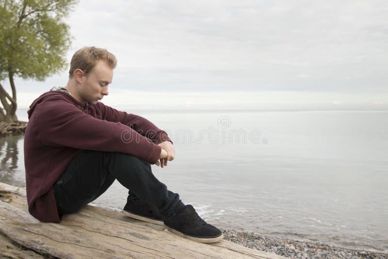 Подросток сидя на журнале и думать стоковое фото