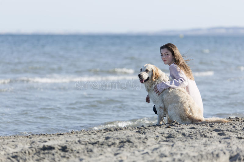 Подросток с ее собакой на пляже стоковые изображения rf