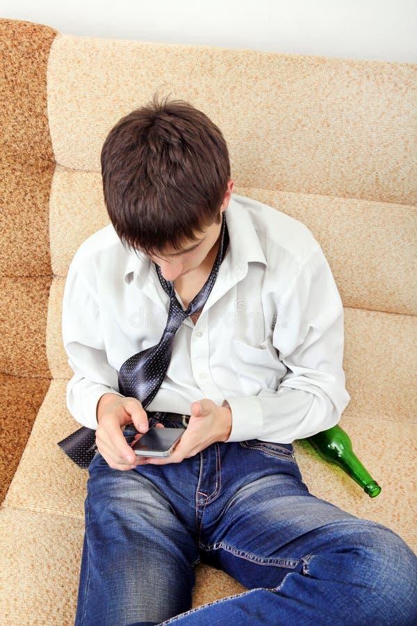 Подросток с пивом и мобильным телефоном стоковая фотография
