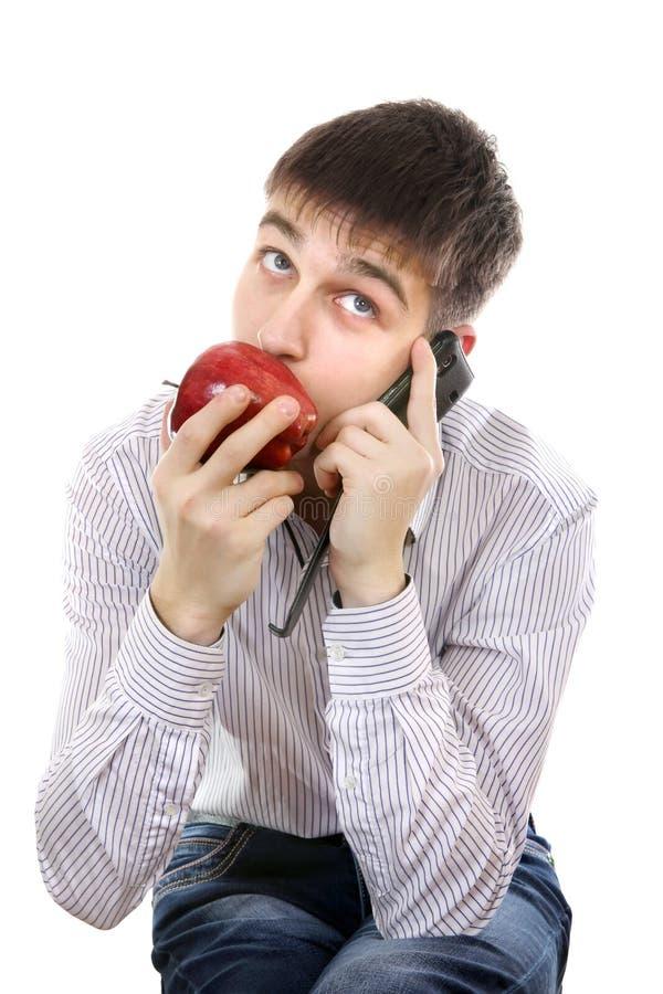 Подросток с Яблоком и мобильным телефоном стоковое изображение rf