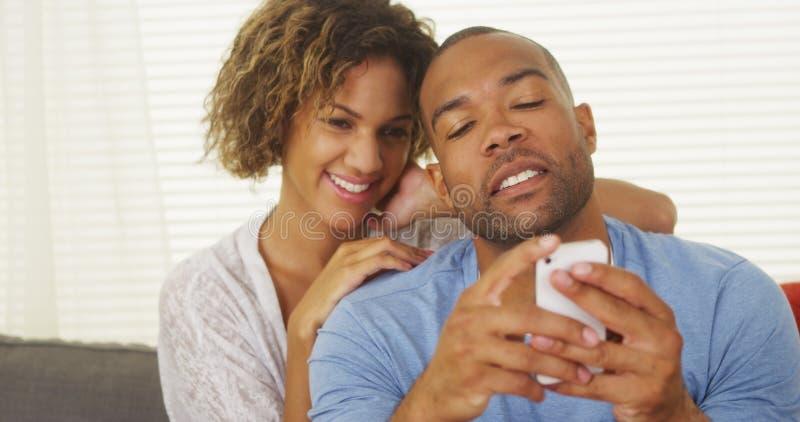 Подруга наблюдая над плечом парня как он отправляет СМС стоковые изображения