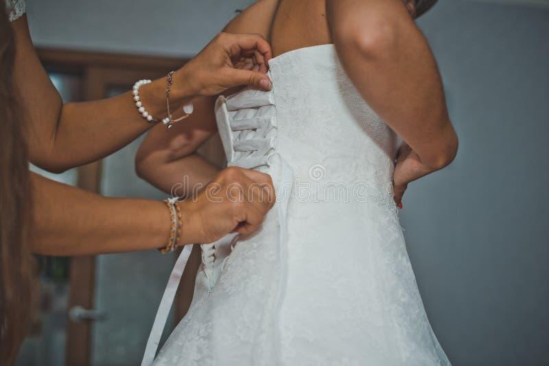 Подруга невесты помогает одеть платье 1914 стоковые фотографии rf