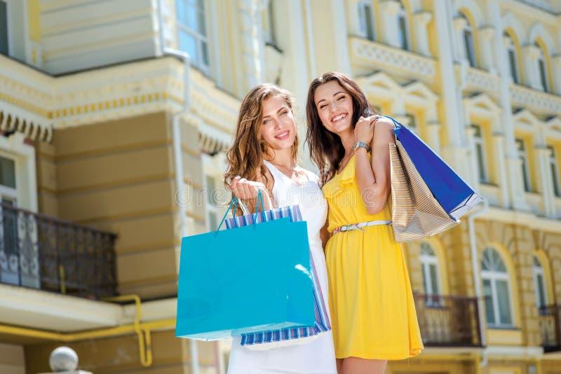 Подруга пришла из магазина счастливого Держать 2 подруг стоковая фотография rf