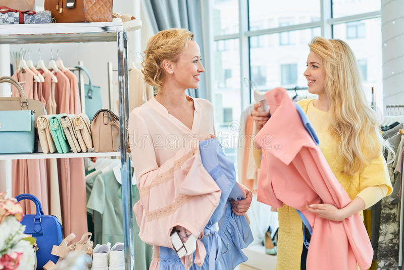 2 подруги встречанной в магазине одежды стоковые фотографии rf