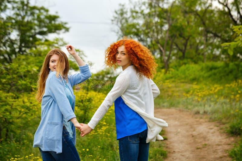 Подруги гуляют рука об руку стоковое фото rf