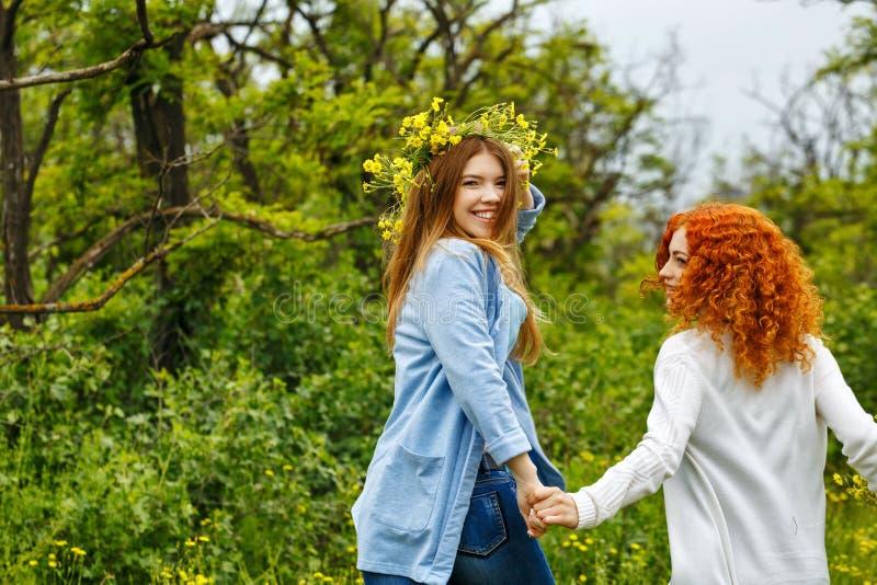 Подруги держа руки и идти стоковые фотографии rf