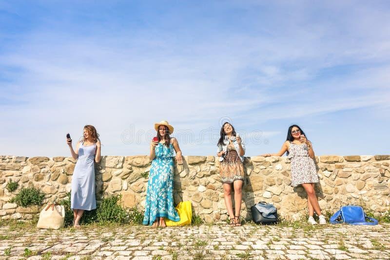 Подруги молодых женщин используя smartphone outdoors стоковое изображение