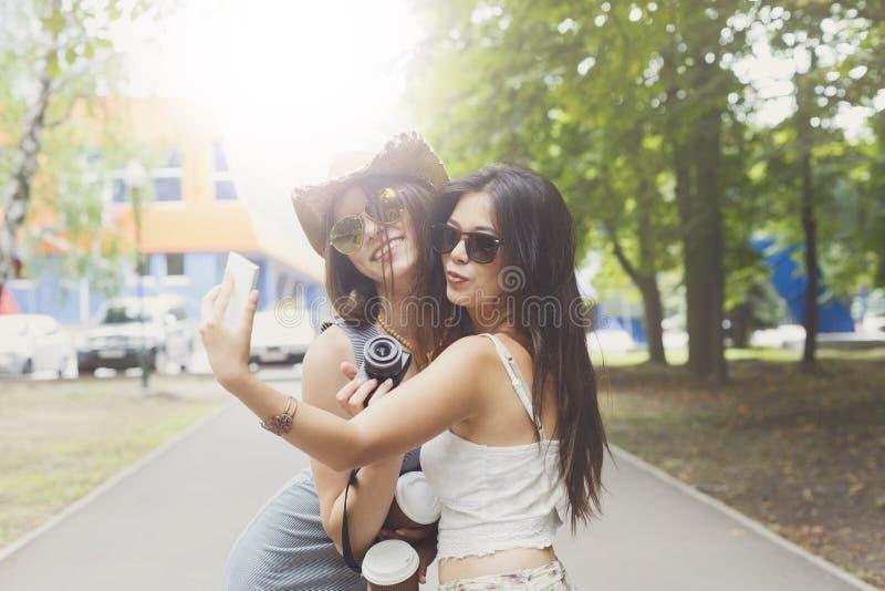 Подруги принимая фото selfie с smartphone outdoors стоковая фотография rf
