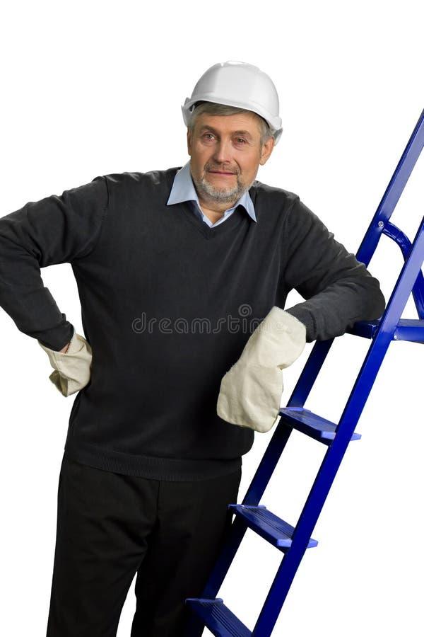 Подрядчик в шлеме и перчатки полагаясь на лестнице стоковое фото