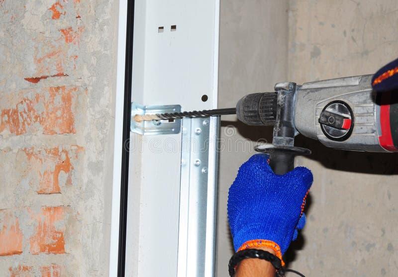 Подрядчик устанавливая дверь гаража Отвертка пользы ремонтника автоматическая для того чтобы просверлить стену для установки двер стоковое фото