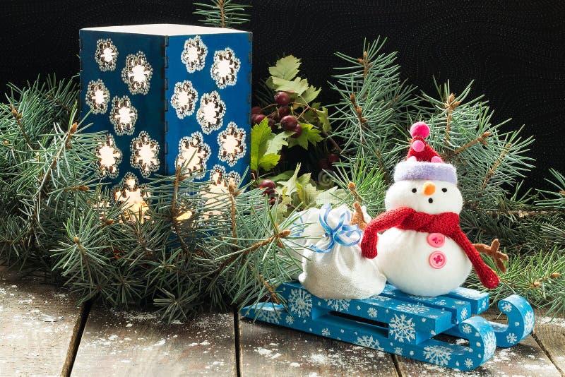 Подсвечник в ветвях спруса и снеговик с сумкой на s стоковые изображения