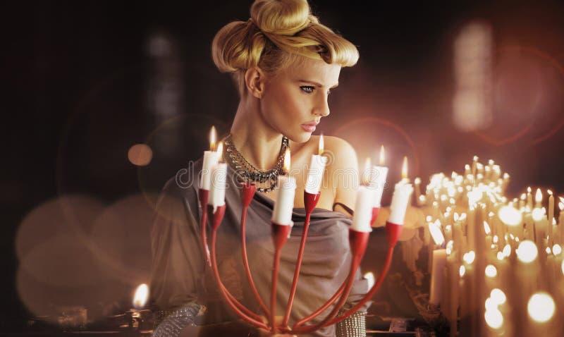 Подсвечник серьезной белокурой привлекательной женщины keping стоковое фото