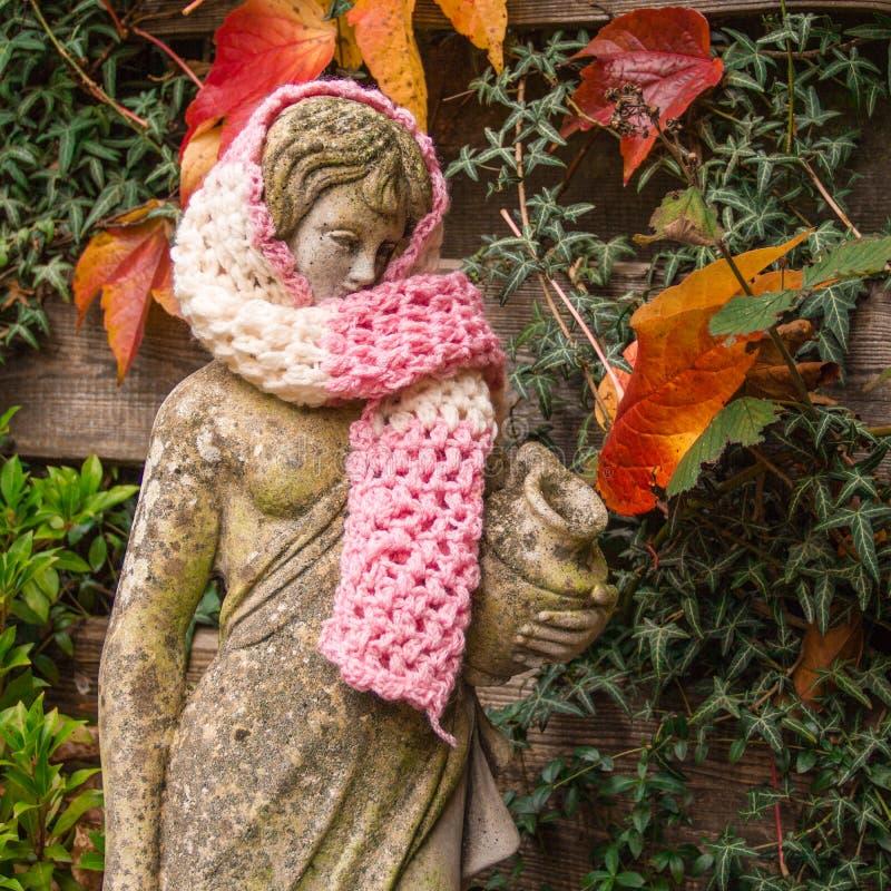 Получать холод, скульптура сада в шерстяном шарфе стоковые фотографии rf