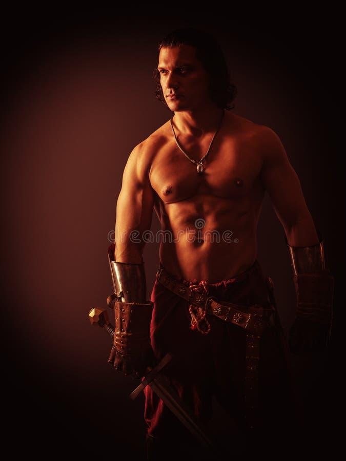 Полу-нагой ратник с шпагой в средневековых одеждах стоковая фотография