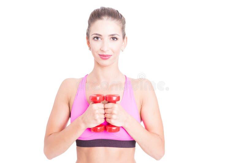 Подходящая женщина держа пару красных гантелей стоковые фотографии rf