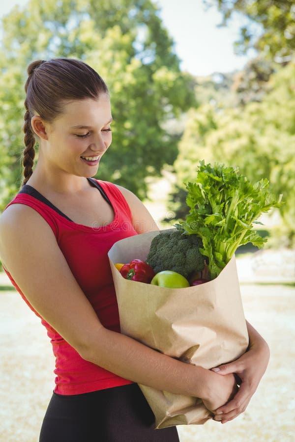 Подходящая женщина держа сумку здоровых бакалей стоковое изображение rf