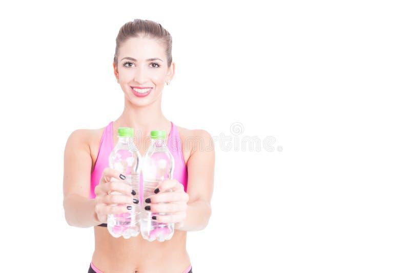 Подходящая женщина показывая 2 бутылки воды стоковые изображения rf