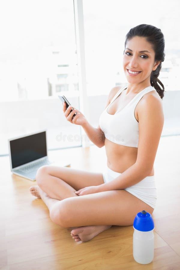 Download Подходящая женщина посылая текст усмехаясь на камере Стоковое Изображение - изображение насчитывающей физическо, актеров: 33739671