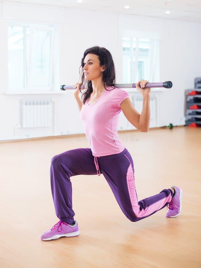 Подходящая женщина работая в фитнес-клубе делая выпад сидит на корточках с штангой на ее плечах стоковые изображения rf