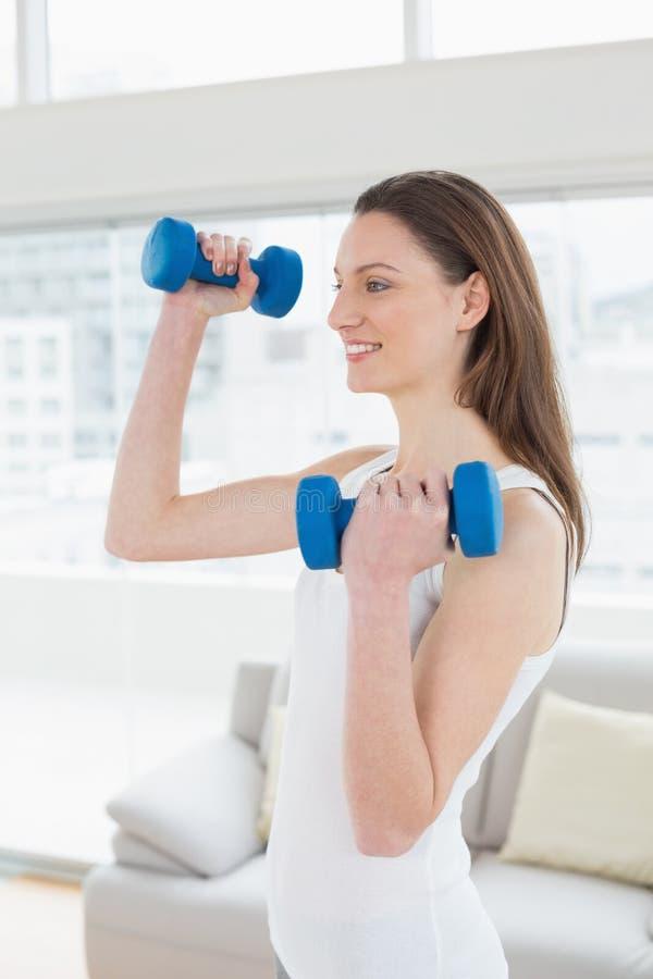 Подходящая женщина работая с гантелями в студии фитнеса стоковые фото