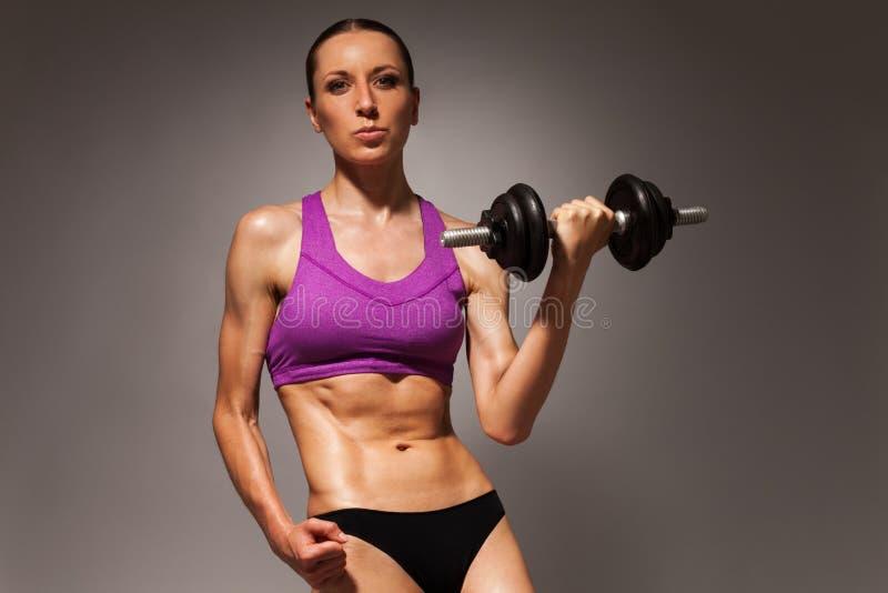 Подходящая молодая женщина с гантелью и плоским abs стоковое изображение rf