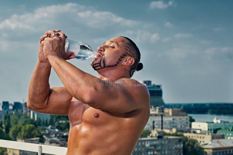Подходящая питьевая вода молодого человека стоковые изображения rf