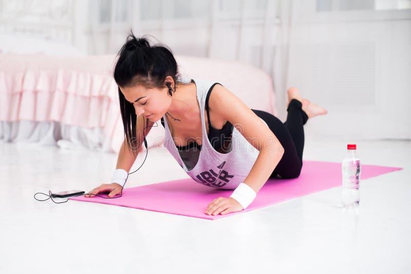 Подходящая sporty женщина в наушниках делать нажимает поднимает музыку домашней тренировки слушая на фитнесе crossfit концепции s стоковая фотография