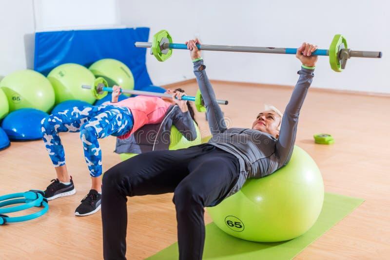 Подходящие женские спортсменки делая комод штанги отжимают тренировку лежа на шарике стабильности в спортзале стоковые фото