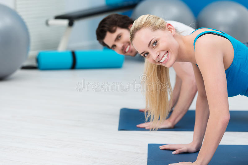 Подходящие молодые пары разрабатывая на спортзале стоковое изображение rf