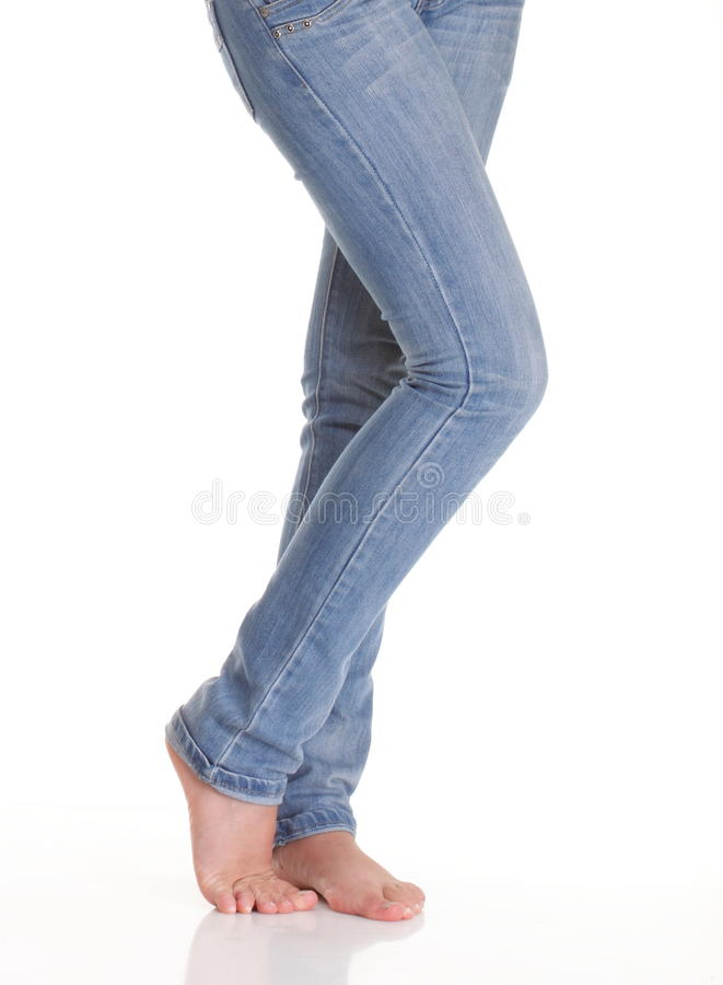 Подходящие ноги женского тела в голубых джинсах, изолированных на белизне стоковая фотография rf