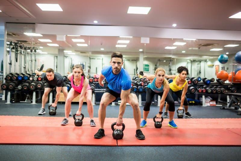 Подходящие люди разрабатывая в классе фитнеса стоковое изображение