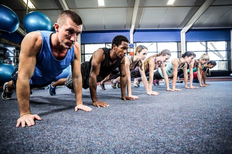 Подходящие люди разрабатывая в классе фитнеса стоковые изображения rf