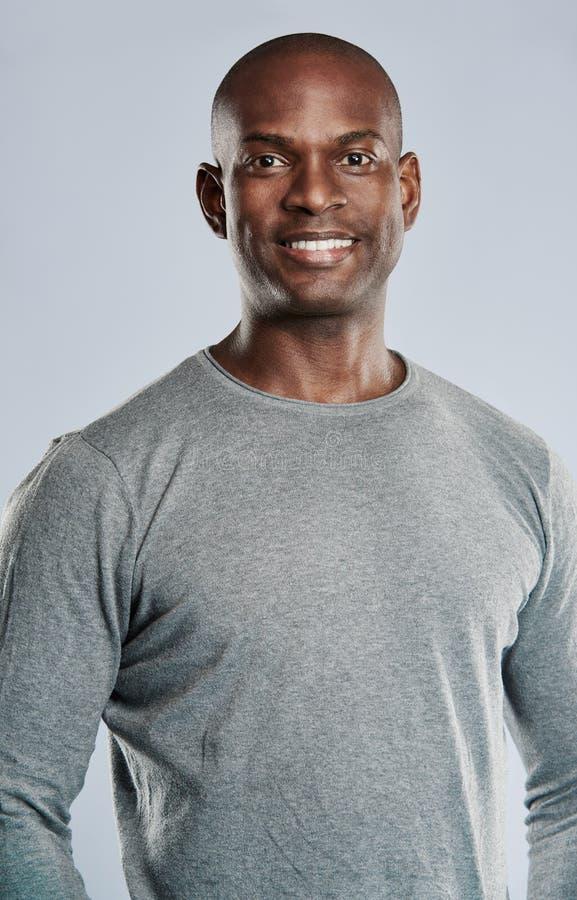 Подходящий красивый усмехаясь человек в серой рубашке стоковое фото rf