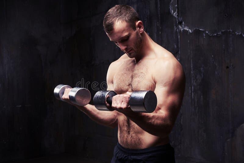 Подходящий спортсмен показывая его вышколенные бицепс и трицепс с dum стоковая фотография rf